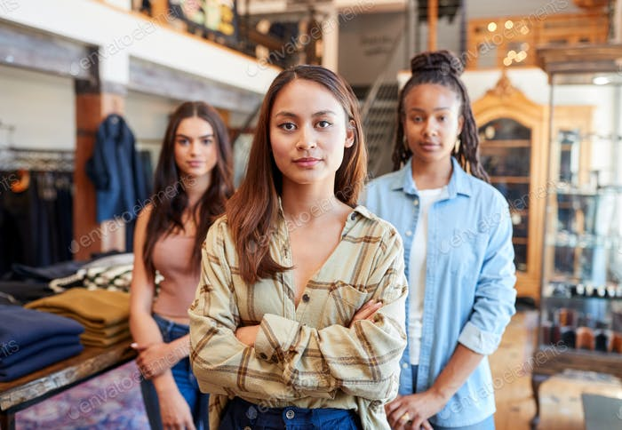 Portrait Of Multi-Cultural Female Sales Team In Fashion Store Standing In Front Of Clothing Display