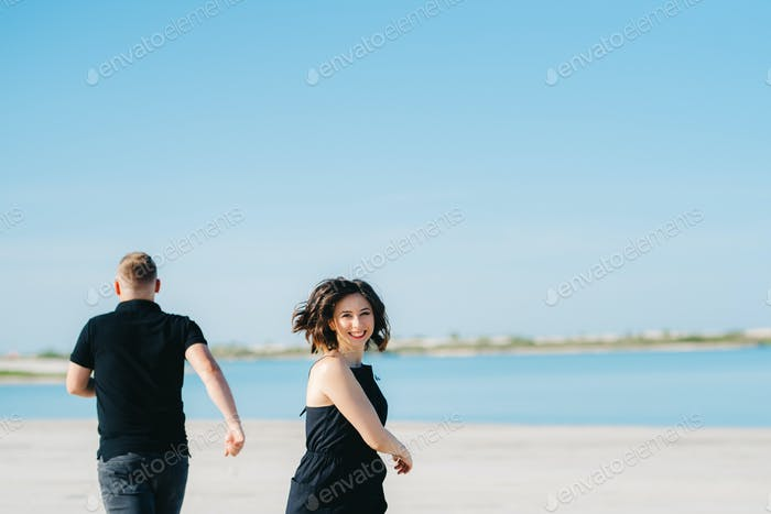 young couple a guy with a girl in black clothes are walking on the white sand
