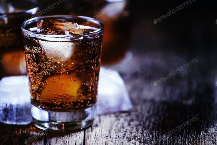 Alcoholic cocktail bourbon cola with whiskey and ice cubes