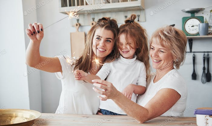 Holiday sparks. Mother, grandmother and daughter having good time in the kitchen