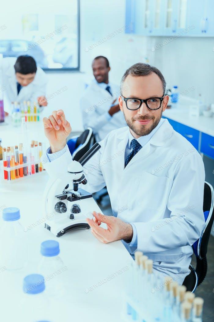 médicos jóvenes en uniforme que trabajan en laboratorio de pruebas, laboratorio químico