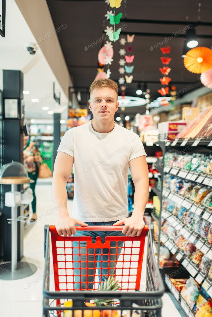 Male customer with cart in food store