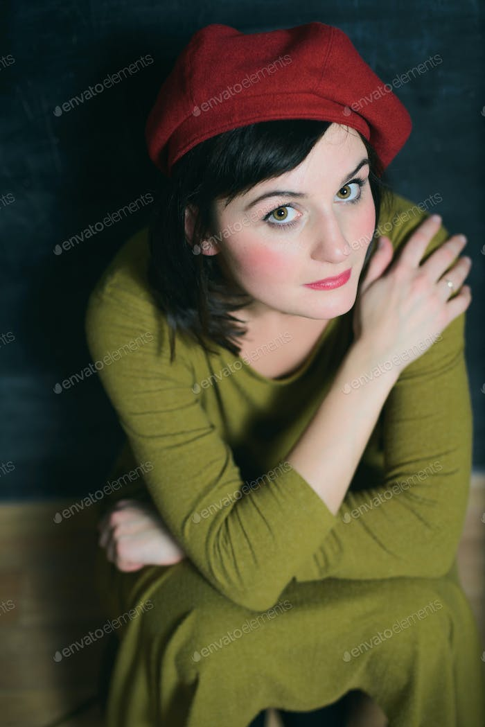 woman in green dress and red beret sitting near the black wall