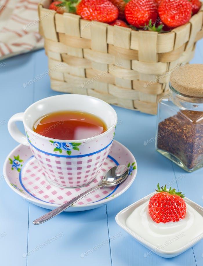 Eine Tasse Rotbuschtee mit einem Erdbeer-Joghurt-Dessert