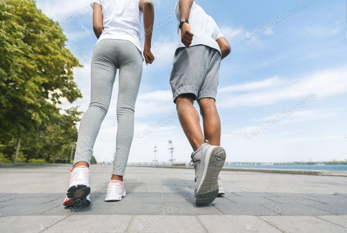 Unrecognizable Black Couple Jogging Along River Bank, Low-Angle, Rear View