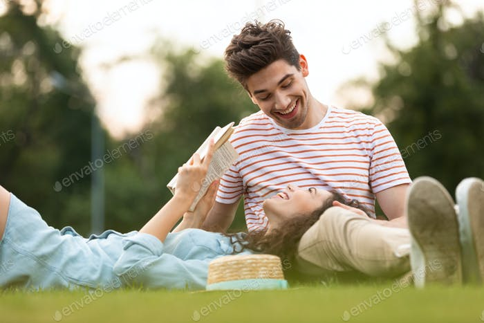 Image of happy couple man and woman 20s lying on green grass in