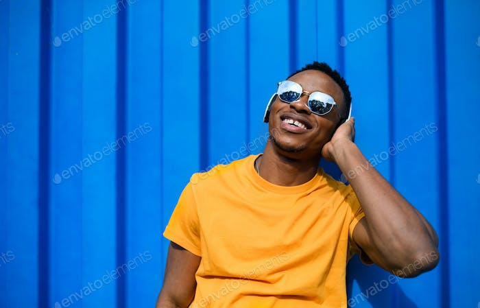 Young black man with sunglasses standing against blue background, black lives matter concept