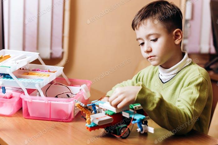 Junge in grünen Pullover gekleidet sitzt am Schreibtisch mit Computer und schaut auf den Roboter, den er aus gemacht