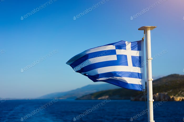 Flag of Greece waving over the see on cruise sheep in front of beautiful coastline