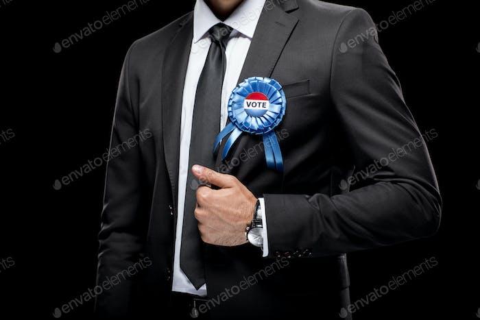 vista recortada del hombre de negocios en traje negro con insignia de voto, aislado en negro