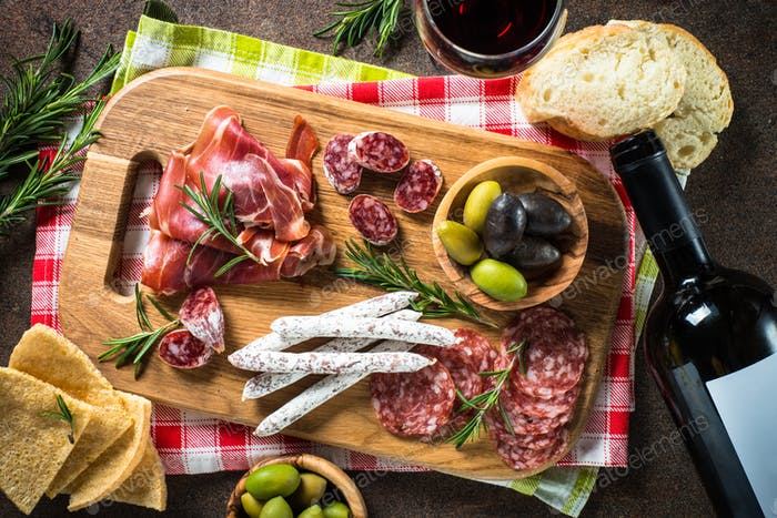 Antipasto - sliced meat, ham, salami, olives on dark stone table top view