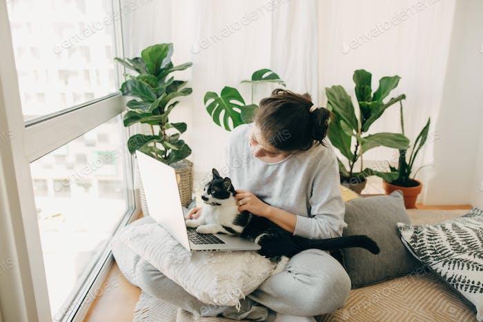 Casual Mädchen arbeiten auf Laptop mit ihrer Katze, sitzen zusammen in modernen Raum mit Kissen und Pflanzen