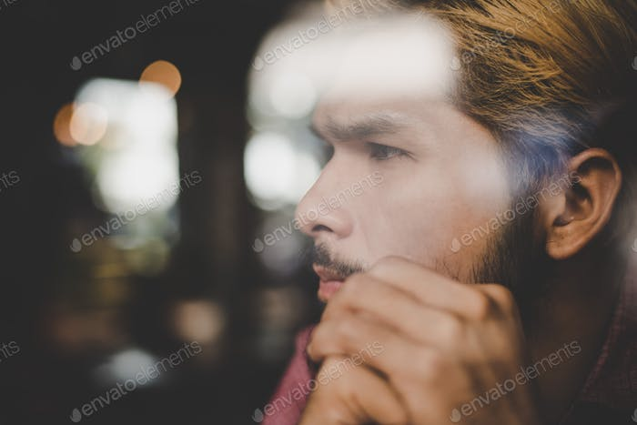 Pensive young hipster man sitting in coffee shop thinking and looking away.