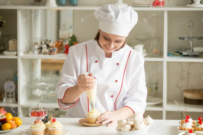 Portrait of confectioner topping a cupcake with cream