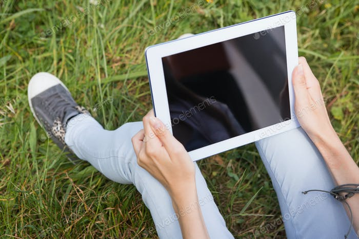 Woman using a tablet in the park on a sunny day