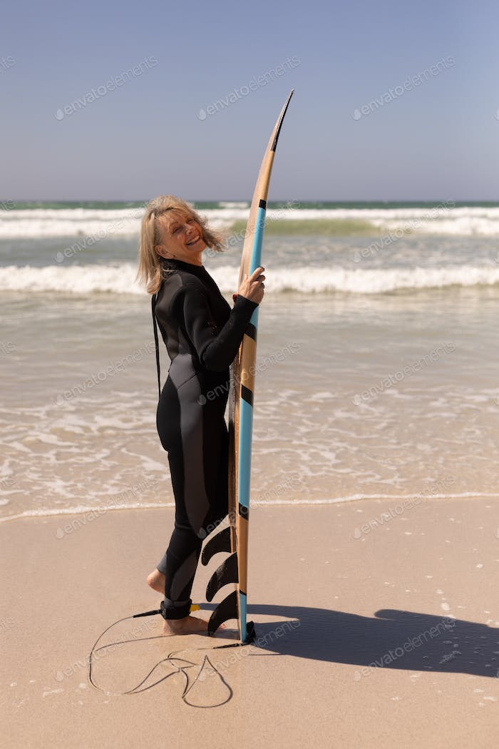 Side view of active senior female surfer standing with surfboard on the beach