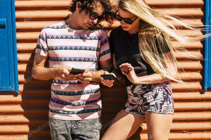 Young caucasian couple use modern cellular phone