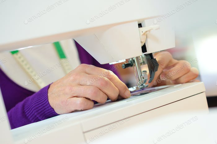 Closeup of woman using sewing machine