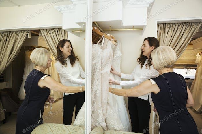 Zwei Frauen, eine Klientin und Einzelhandelsberaterin in einem Hochzeitskleidgeschäft, suchen durch die Wahl der Kleider.