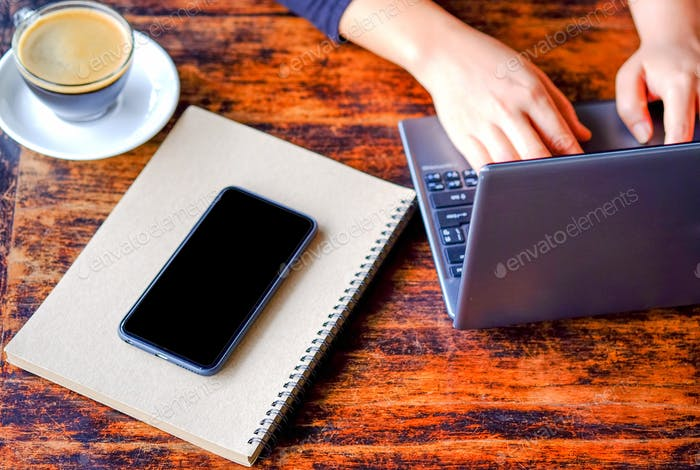 Women working laptop with coffee and smart phone on notebook.