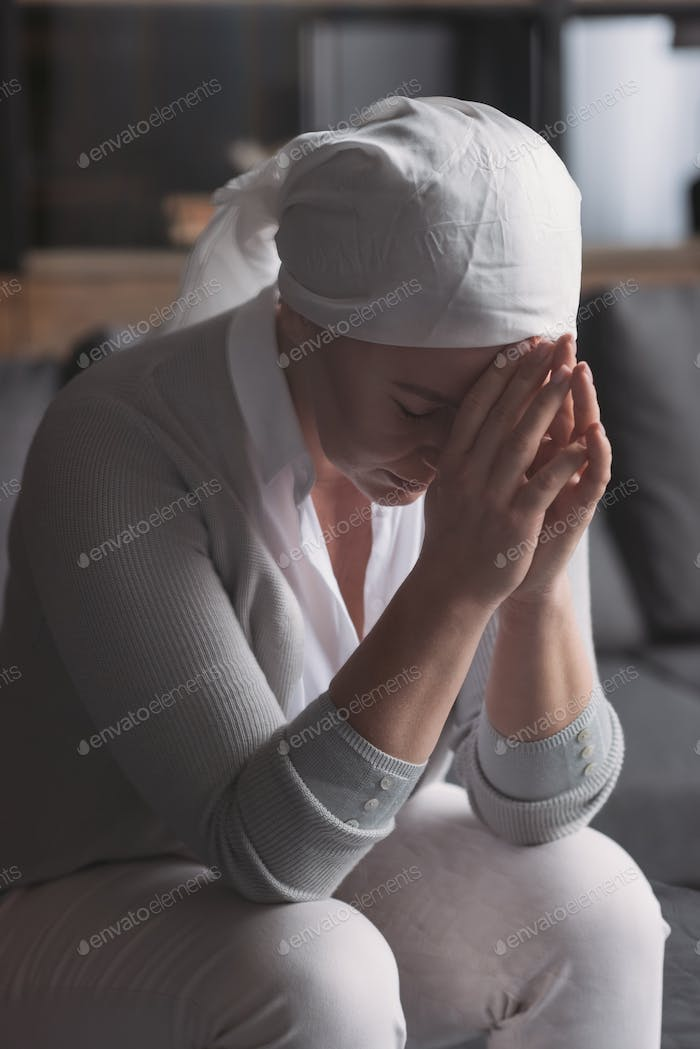 upset sick mature woman in kerchief sitting at home, cancer concept