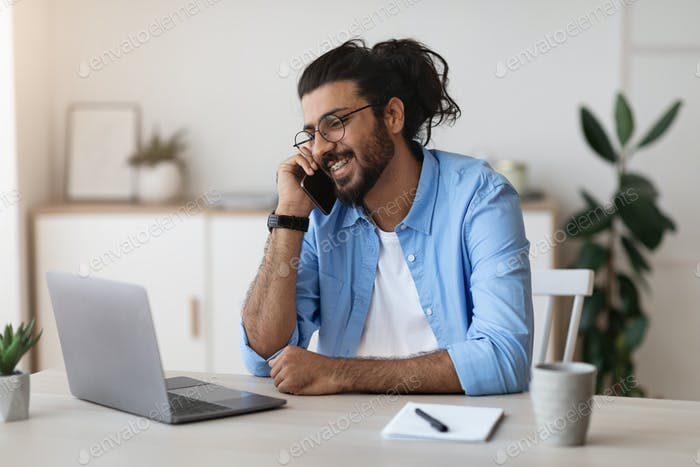 Western Freelancer Guy Talking On Cellphone And Working On Laptop At Home