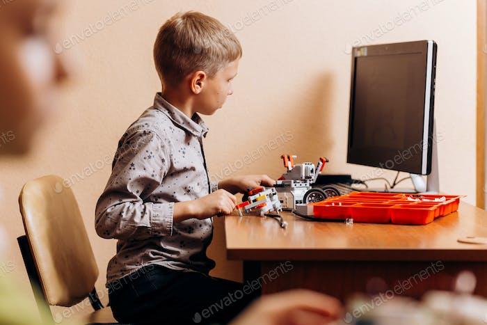 Fleißiger Junge in grauem Hemd gekleidet macht einen Roboter aus dem Roboter-Konstruktor am Schreibtisch mit