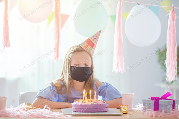 Caucasian girl wear a mask on her birthday. Festive colorful background with balloons. Birthday