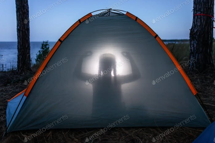 Girl meditating on sunset in the camping tent in summer. Local tourism and mental recreation