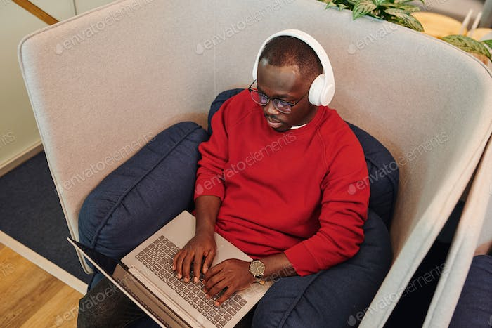 Young African male office manager or designer in headphones using laptop
