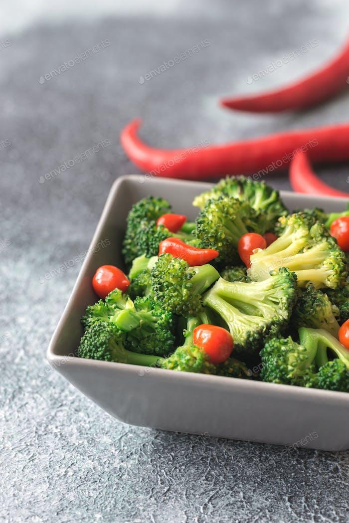 Schüssel mit Brokkoli und Chili braten auf grauem Hintergrund