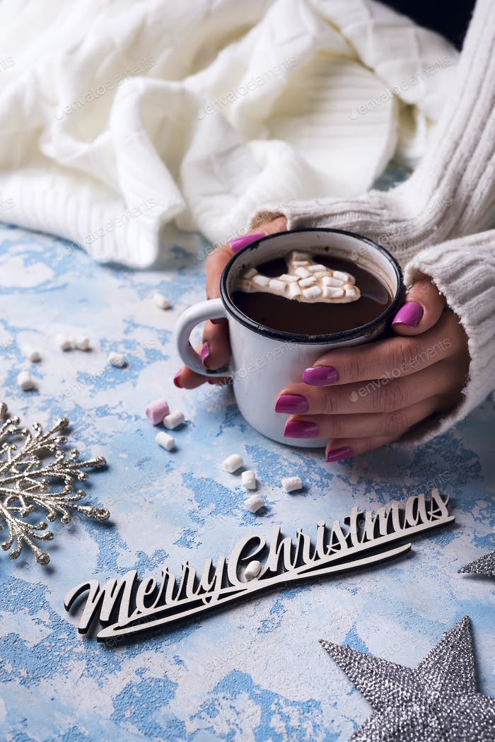 female hand holding cup of hot cocoa