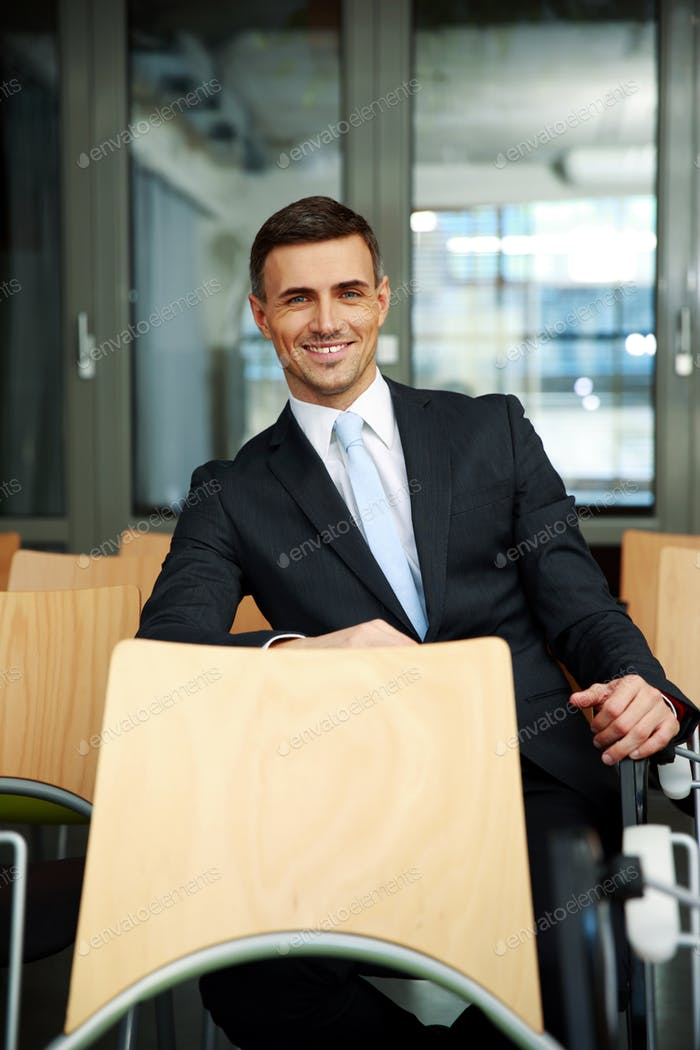 Smiling businessman sitting at conference hall