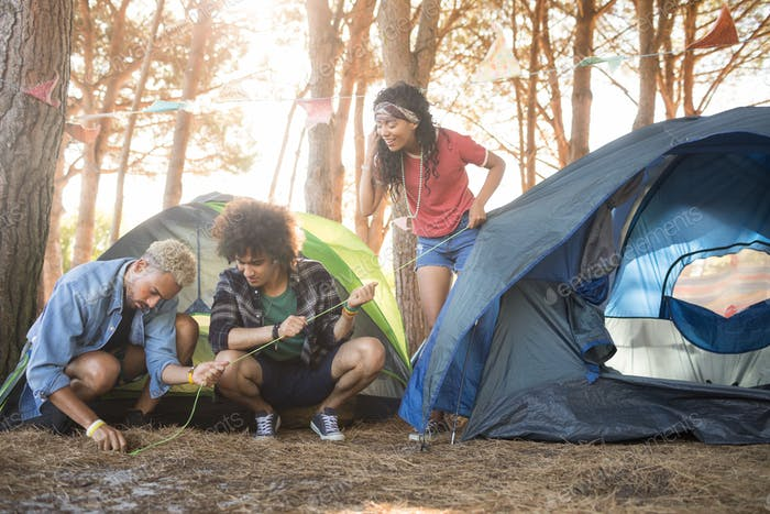 Young friends setting up tent at forest