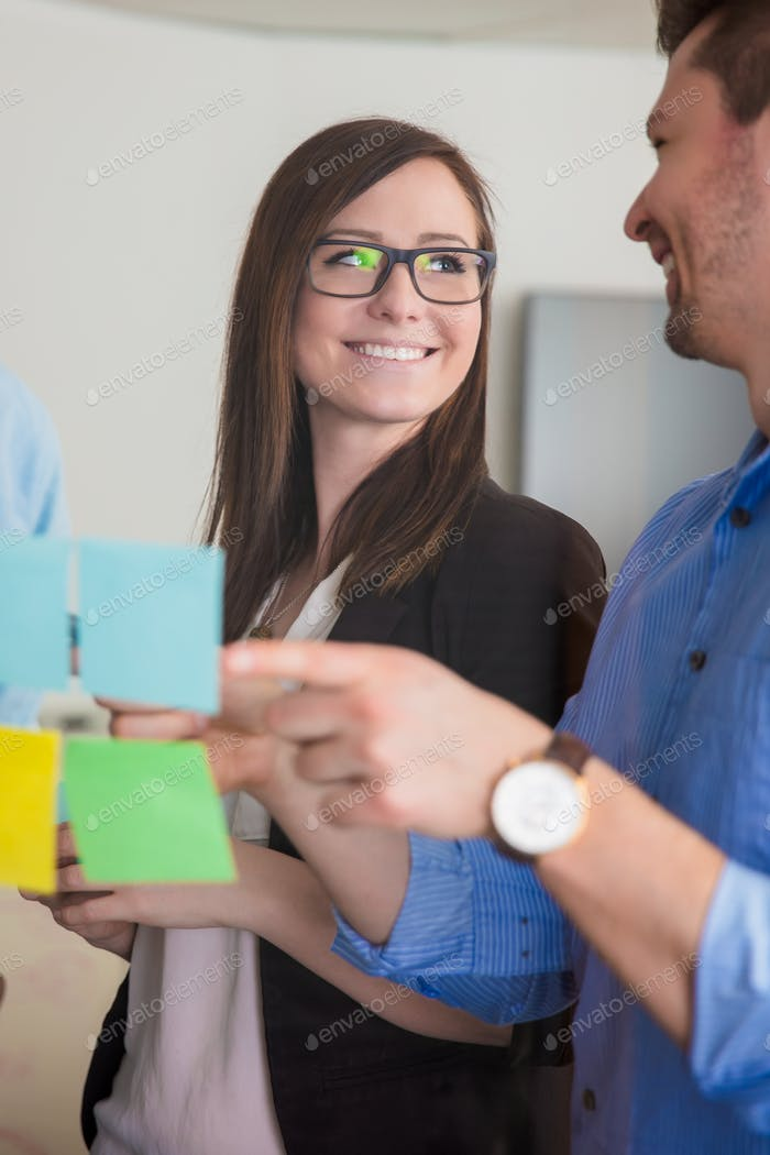 Businesswoman Looking At Colleague While Discussing Over Notes O