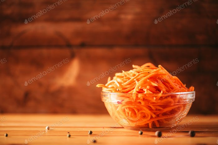 Spicy korean carrot salad on wooden background. Copy space. Koryo-saram cuisine