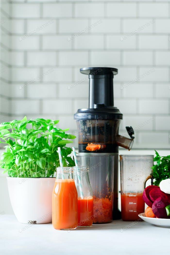 Frau, die frisches Getränk macht. Saftpresse und Karottensaft. Früchte im Hintergrund. Sauberes Essen, Entgiftungskonzept