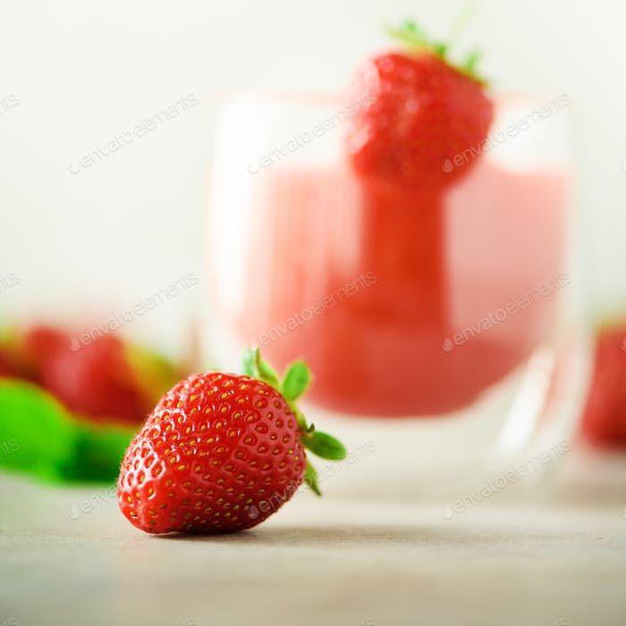 Glass with vegan strawberry smoothie on grey background with copy space. Square crop. Summer food