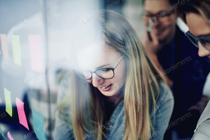 Smiling businesswoman brainstorming with coworkers on an office window