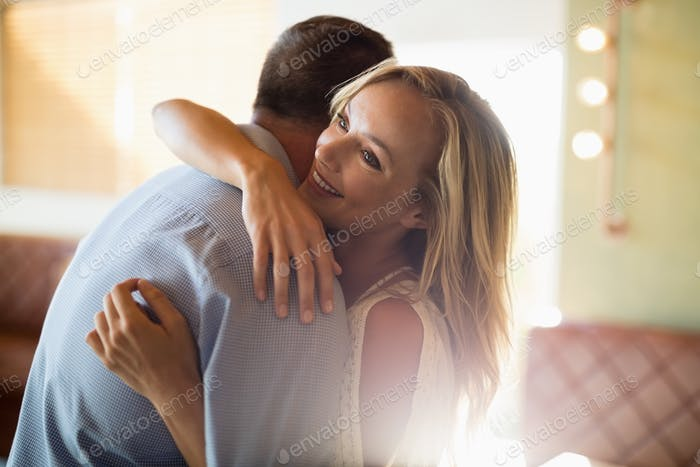 Couple embracing each other in restaurant