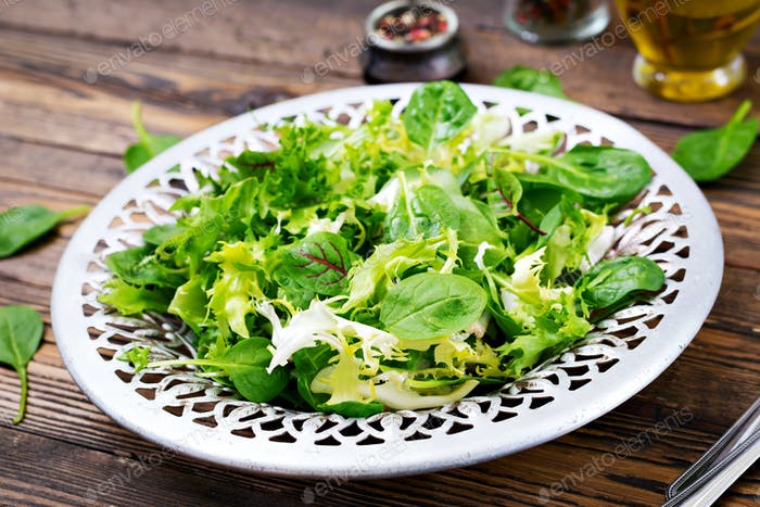 Fresh leaves of mix salad in a bowl on a wooden background