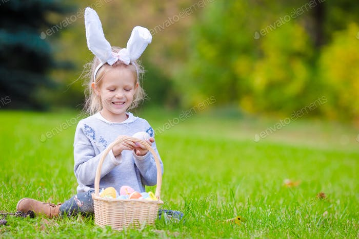 Portrait of little kid wearing bunny ears with a basket full of Easter eggs on spring day outdoors