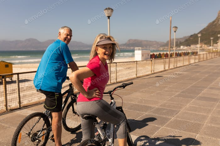 Rear view of active senior couple riding a bicycle on a promenade at beach