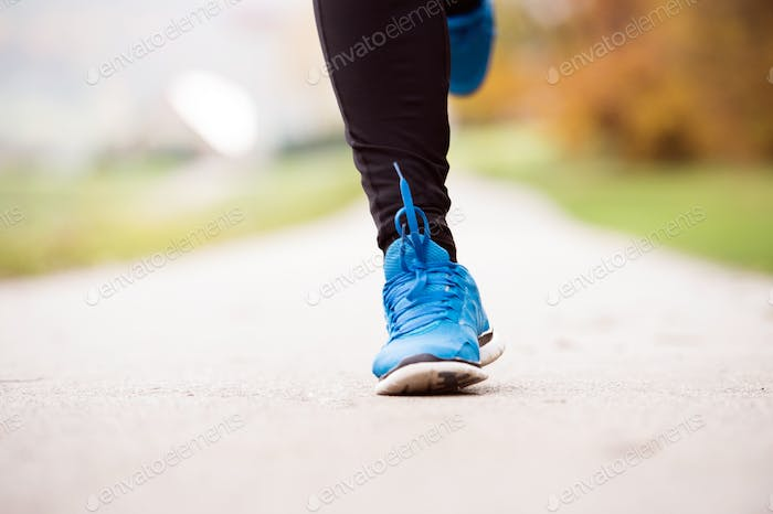 Legs of unrecognizable runner jogging on concrete path,close up