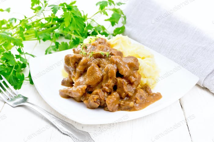 Goulash of beef with mashed potatoes in plate on wooden board
