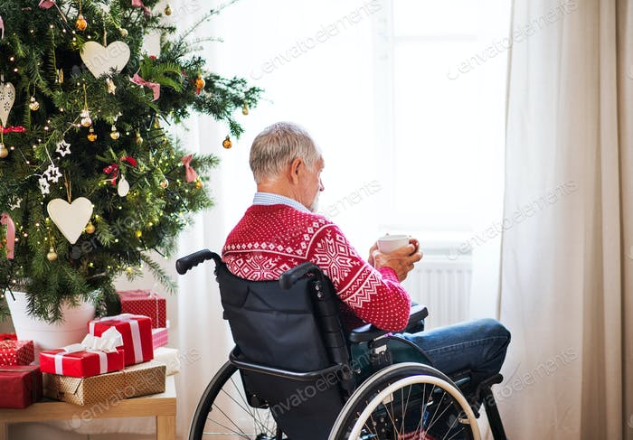 A senior man in wheelchair with a cup of tea or coffee at home at Christmas time.