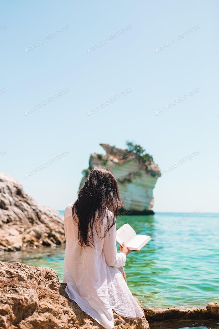 Junge Frau liest am tropischen weißen Strand
