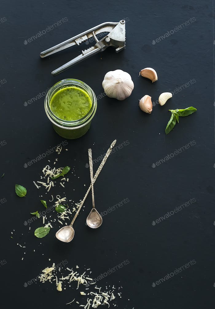 Jar of fresh home made pesto with ingredients for it