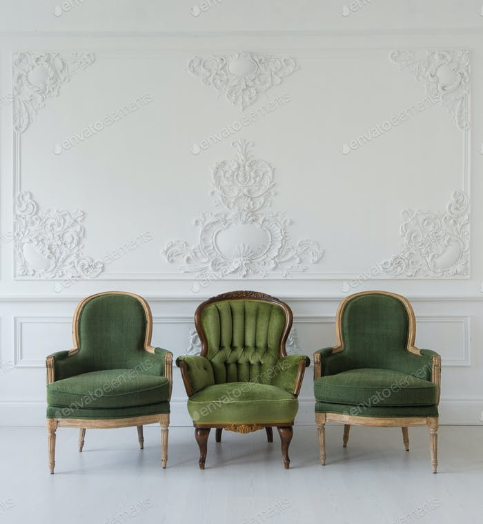 Set of green wooden vintage chairs standing in front a white wall design bas-relief stucco mouldings