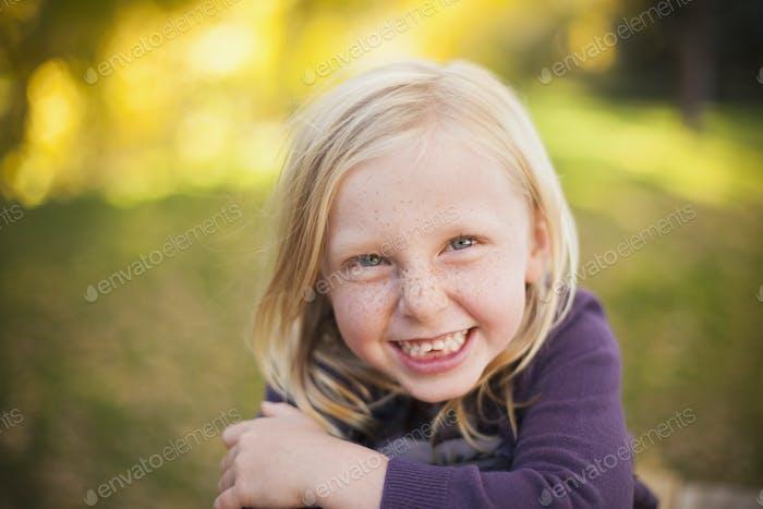 Una chica sentada en la hierba, sonriendo una gran sonrisa con dientes. ¡Cierren!